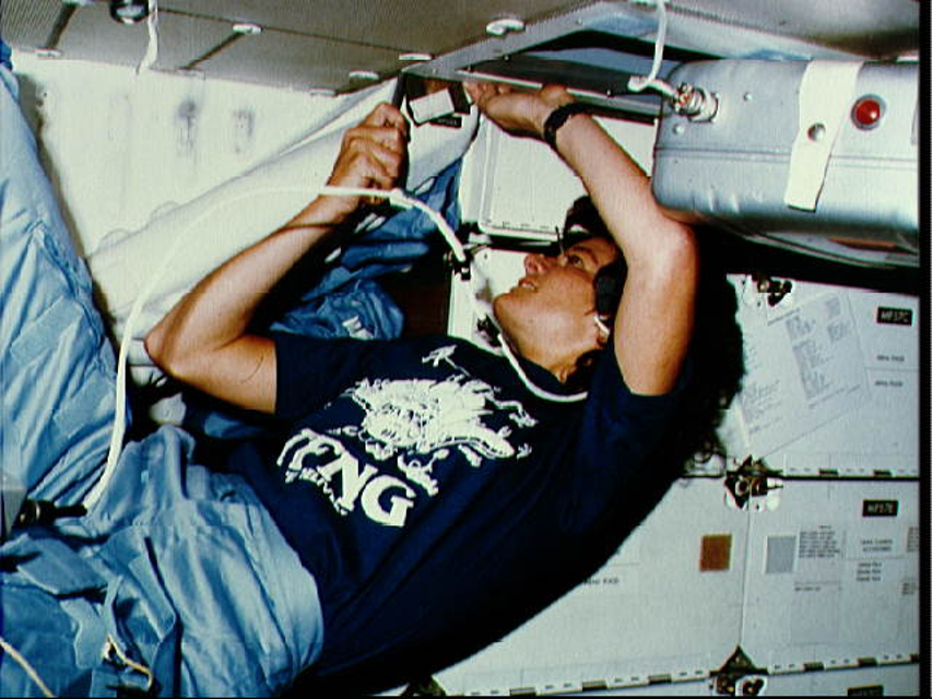 Dr. Sally K. Ride on the middeck of the Space Shuttle Challenger. Her shirt features a cartoon of 35 busy astronauts around a shuttle with the acronym TFNG, which stands for thirty five new guys, a nickname for the 1978 astronaut class.